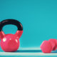 Pink kettlebell and dumbbell on a blue gradient background